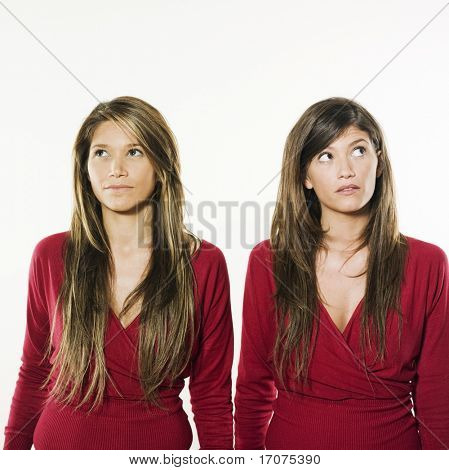 studio shot portrait on isolated background of two sisters twin women friends thinking looking up