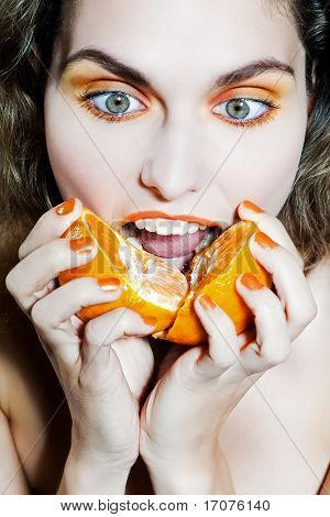 studio portrait of a beautiful woman holding orange mandarine citrus frui