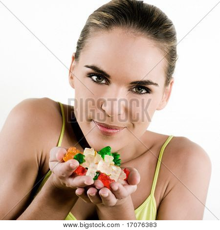 beautiful brunette caucasian woman on white background handful of jellybeans