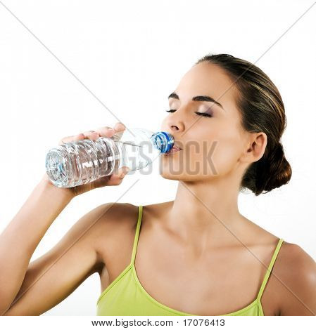 beautiful brunette caucasian woman on white background drinking mineral water in a plastic bottle