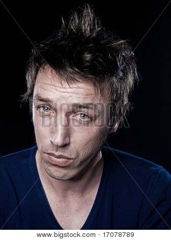 studio portrait on black background of a funny expressive caucasian man puckering displeased