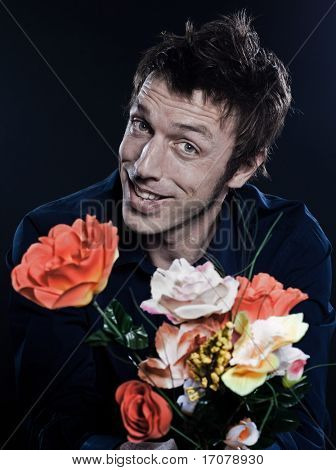 studio portrait on black background of a funny expressive caucasian man offering flowers cheerful seducto