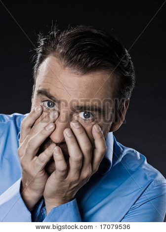 caucasian man unshaven fear hiding portrait isolated studio on black background