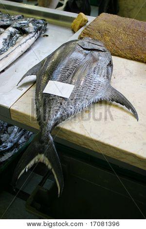 Atún en la losa de un pescadero con boleto del precio