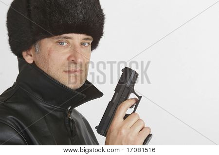 A man in Russian clothing complete with a 9mm automatic handgun