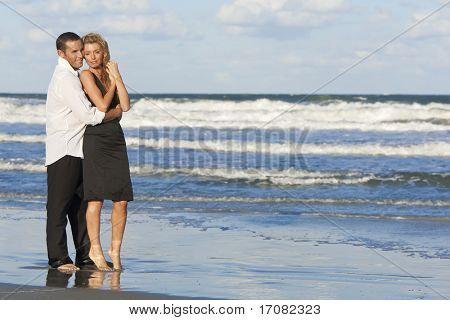 A young man and woman embracing as a romantic couple standing in the sea on a beach with a blue sky