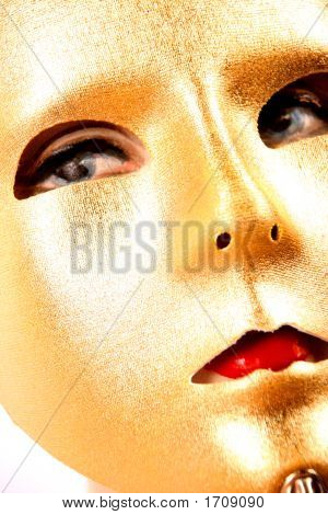 Golden Mask On A Stick For A Masquerade Ball With A Female Mannequin With Red Lips In Behind