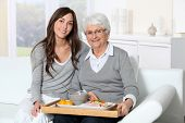 Elderly woman and home carer sitting in sofa with lunch tray