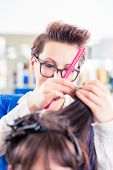 Female coiffeur divide women hair in sections with clips in shop poster