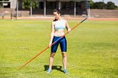 Постер, плакат: Female athlete holding a javelin in stadium on a sunny day