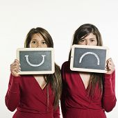 studio shot portrait on isolated background of two sisters twin women friends expressing positivity