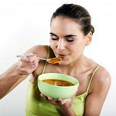 Постер, плакат: красивая брюнетка Кавказская женщина на белом фоне ест суп
