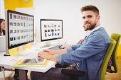 Portrait of confident young male editor working in creative office poster
