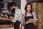 Waitress using a tablet computer and waiter with coffee machine in the bar poster