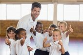 Portrait of sport teacher and students showing thumbs up in school gym poster