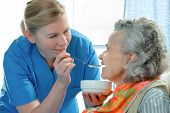 picture of geriatric  - senior woman 90 years old being fed by a nurse - JPG