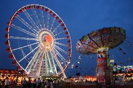 stock photo of swingers  - Carnival giant wheel and wave swinger at the dusk - JPG