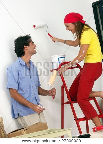 Hispanic couple painting a new house,