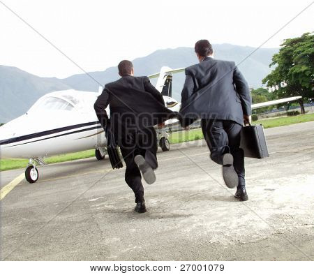 Two businessman running towards a plane.