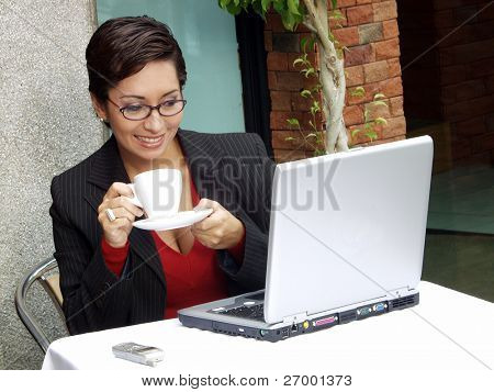 Businesswoman woman in a restaurant working on a computer.
