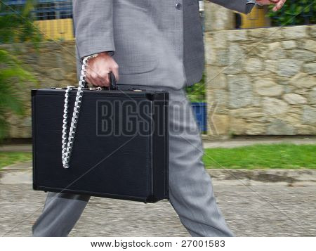 businessman walking with a secure briefcase.   Businessman holding a handcuffs suitcase.