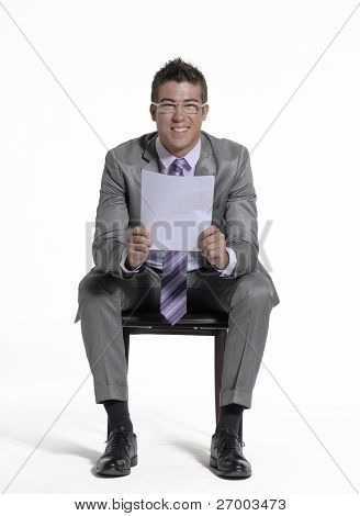 Young businessman sitting and reading a document on white background.