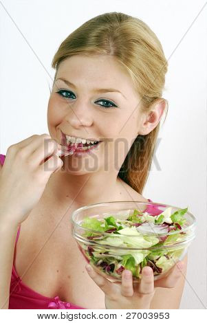 young woman holding a vegetable salad bowl