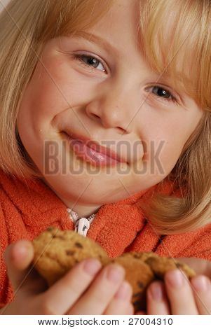 Little girl eating cookies,kid holding cookies.