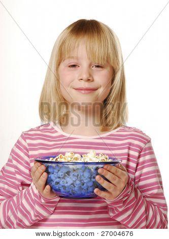 Little girl eating popcorn. Little kid eating pop corn.