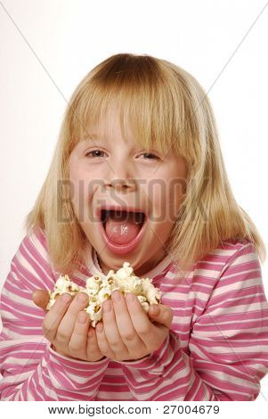 Little girl eating popcorn. Little kid eating pop corn.