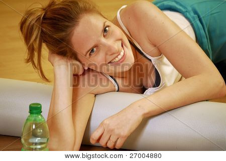 Young blonde woman drinking water after having trained.
