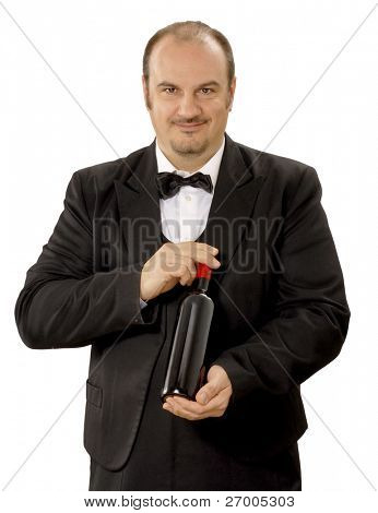 Young sommelier holding a red wine bottle on white background.