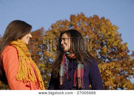 Otoñales jóvenes mujeres de al aire libre disfrutando de un día de cielo azul.