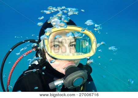 Scuba diver with bubbles looking at copy space for your text.