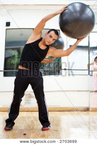 Hombre en el gimnasio haciendo Pilates