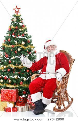 Santa Claus sitting next Christmas tree showing thumb-up sign, isolated on white background