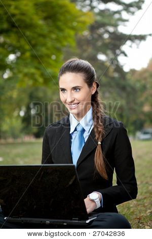 young caucasian  businesswoman working on grass in park