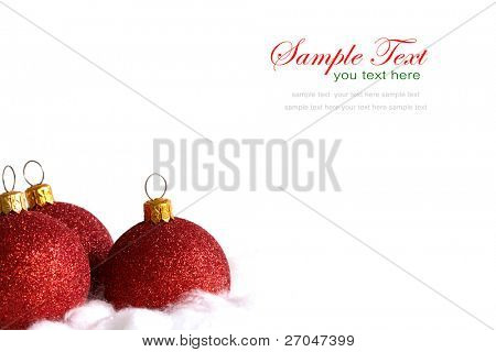 Red christmas balls in billowy feathers with copy space.