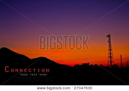 Satellite dishes and communications tower over sunset.