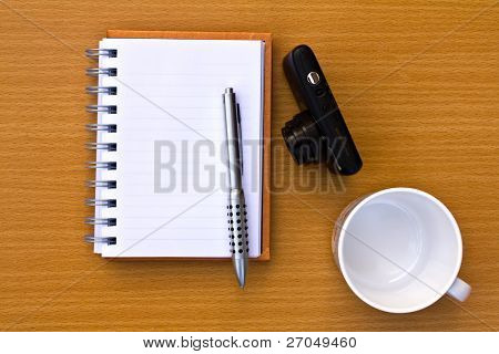 Note book and pen and coffee cup and camera. On the floor of the wooden table.