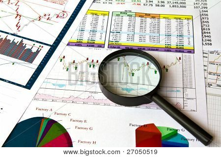 A magnifying glass focusing on a graph in the  financial charts