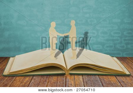 Paper cut of two business man shake hand on old book