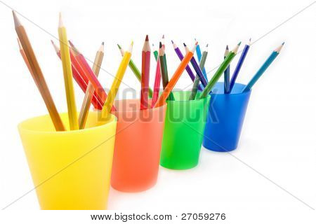 wide angle picture of color pencils in four plastic cups isolated on white