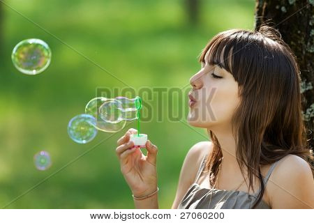pretty teenage girl blowing bubbles soap in nature