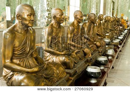 row of golden monk buddhist statues in thai temple, angthong, thailand