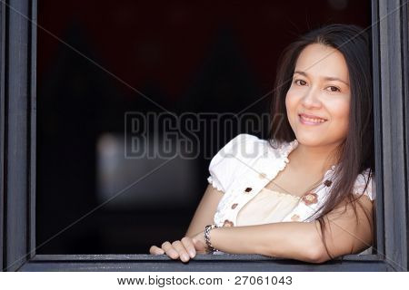 young asian woman leaning at wooden window