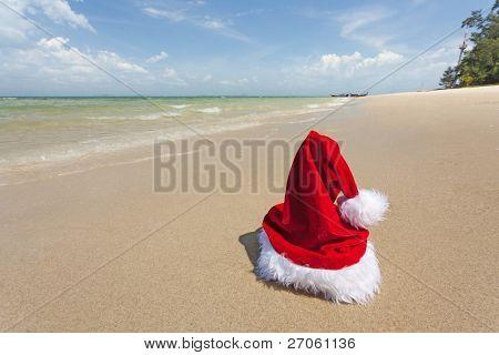 vivid santa hat standing on tropical beach