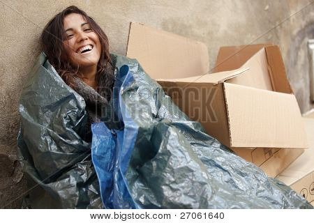 happy poor woman wrapped with tarpaulin