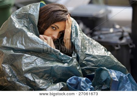 poor young woman wrapped in plastic tarpaulin