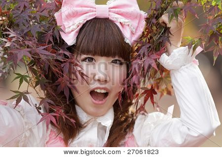 japanese girl in sweet lolita cosplay style in red fall maple,Tokyo